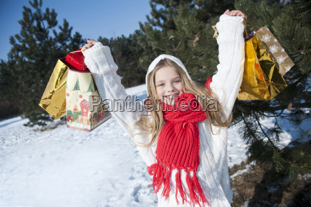 young girl holding up christmas presents