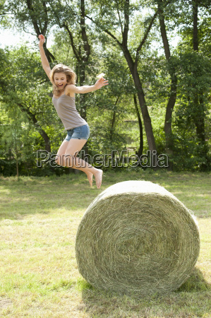young woman jumping from hay bale