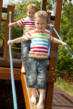 twin brothers walking down wooden beam