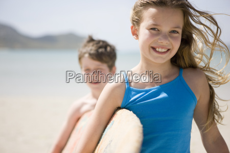 girl and boy carrying surfboard portrait
