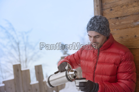 mid adult man pouring drink from
