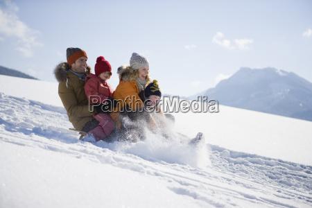 family tobogganing on snow