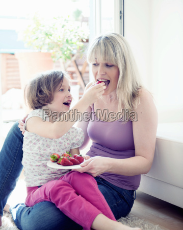 young girl feeding strawberries to mother