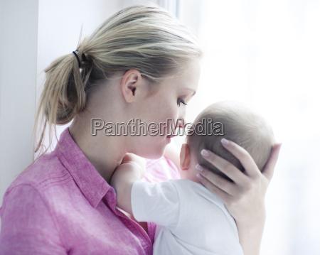 teenage girl holding baby boy close