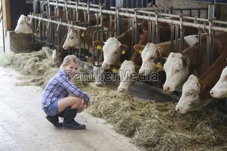 young girl crouching by cattle in