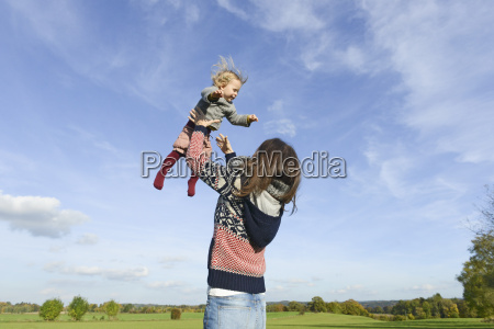 woman playing with granddaughter against blue