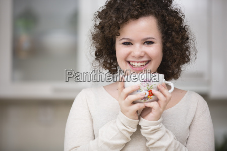 teenage girl holding cup smiling