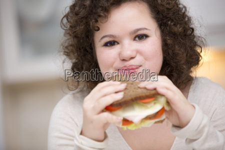 teenage girl eating sandwich portrait