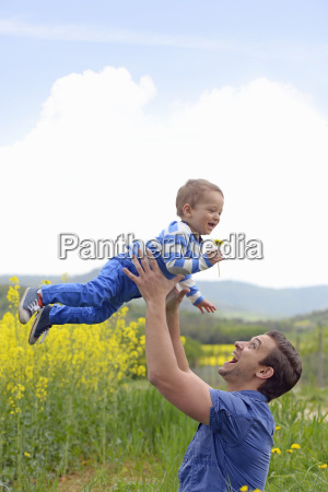 young man holding son aloft in