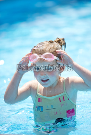 young girl adjusting swimming goggles in