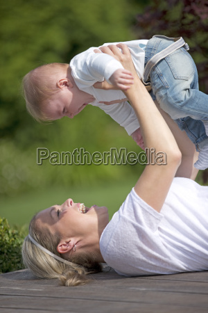 mother lifting baby on decking