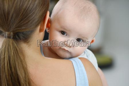 baby boy looking over mothers shoulder