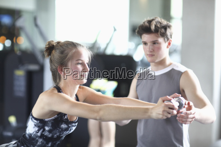 teenage fitness instructor assisting girl in