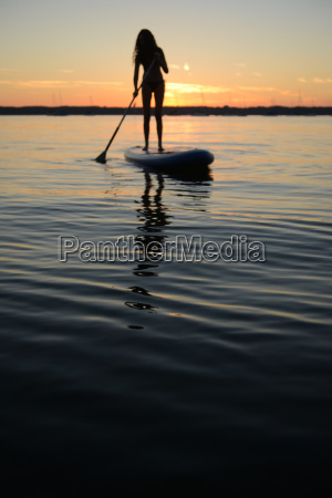 teenage girl on paddleboard at sunset