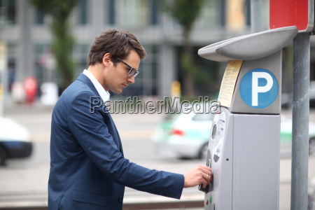mid adult businessman at parking meter