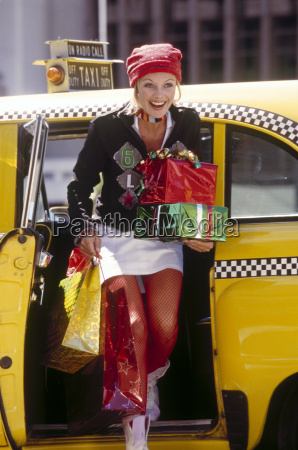 young woman exiting taxi with gift