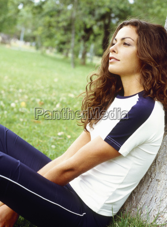 young woman relaxing against tree