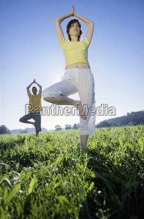 couple practicing yoga in a field