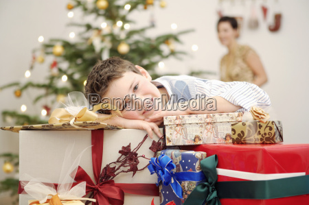 boy leaning on stack of christmas