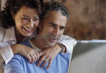 middle aged couple using laptop at