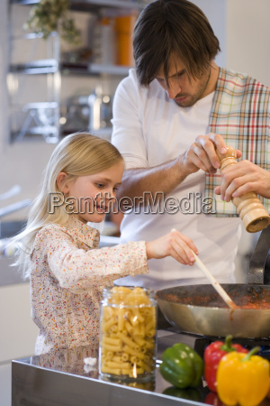young girl helping father cook on