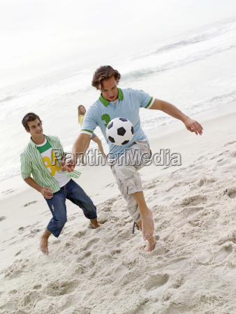 two young men playing with soccer