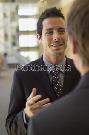 two businessmen talking indoors