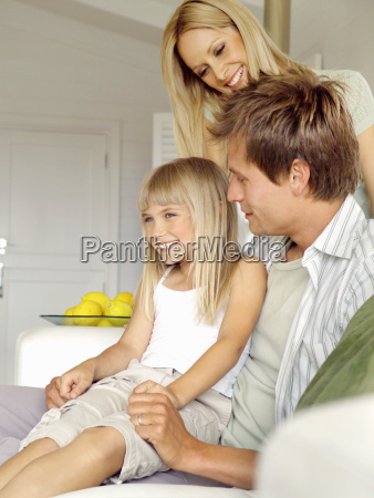 family smiling and sitting on sofa