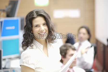 businesswoman smiling with paperwork in office