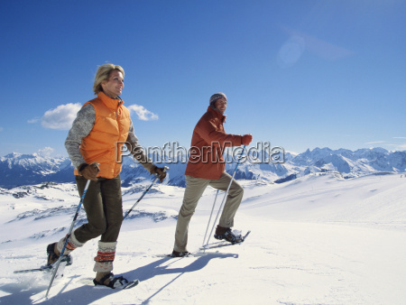 couple snowshoeing with ski poles under