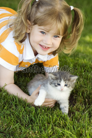 young girl in grass with kitten