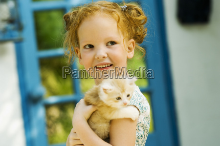 young girl holding kitten outdoors