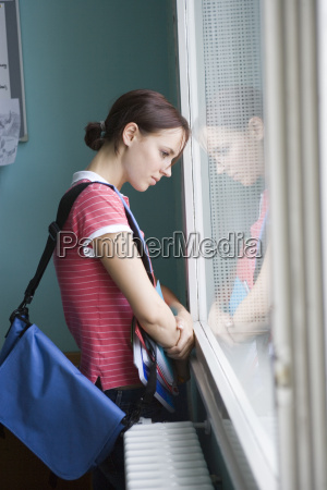 female teenage student looking out window