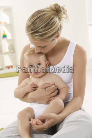 mother kissing baby on head