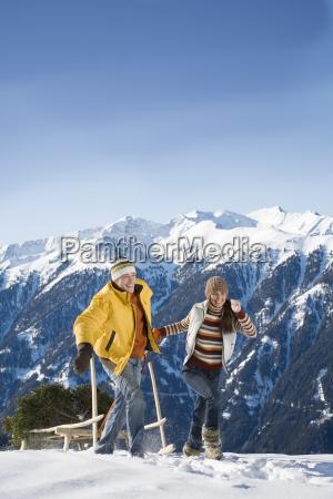 couple pulling pine tree on sled