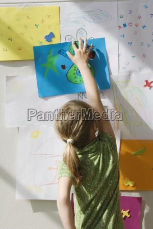 preschool girl putting artwork on wall