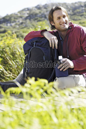 man sitting outdoors with backpack and