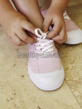 close up of girl tying shoe
