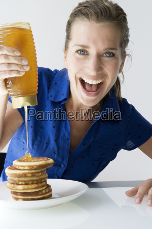 happy woman pouring honey on pancakes