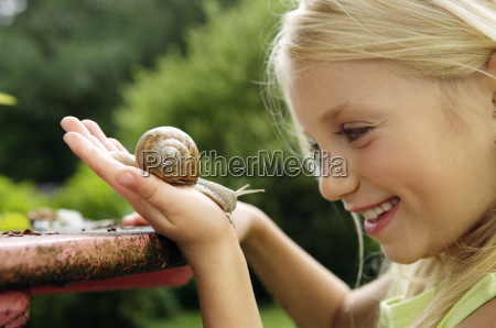 young girl holding snail