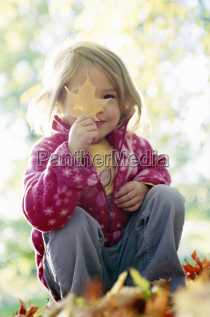 young girl holding autumn leaf up