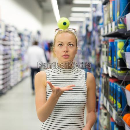 woman shopping tennis balls in sportswear