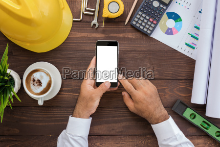 engineering using phone on his workspace