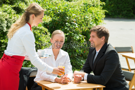 waitress serving glass of juice to