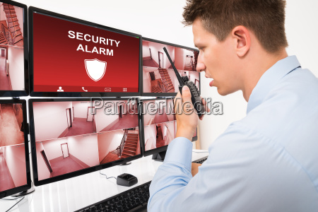 young male security guard using walkie