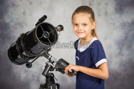 seven year girl adjusts the telescope