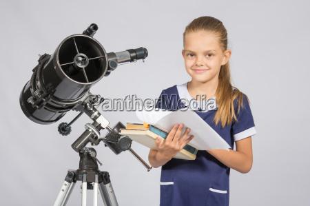 schoolgirl astronomer leafing through books standing