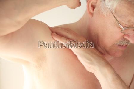 shirtless man with aching shoulder
