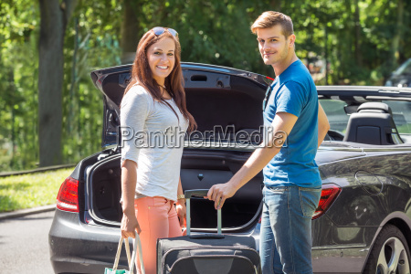 smiling couple putting luggage in a