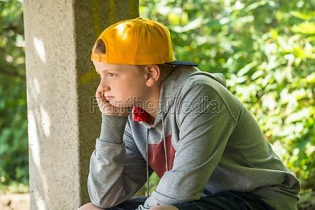 upset junge sitzt im park